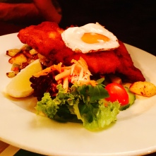 Schnitzel served with roast potatoes, salad and a fried egg